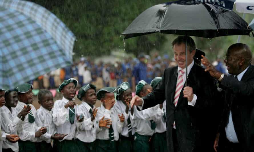 Tony Blair and then Sierra Leone president, Alhaji Tejan Kabbah, pass schoolchildren in heavy rain on a visit to a school in 2007.