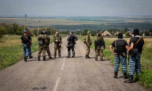 Armed separatist guards during the OSCE monitors visit to MH17 flight crash site in the village of Grabovo, East Ukraine.