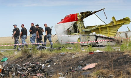Rebel soldiers pass a large piece of debris at the main crash site of MH17 which was shot down over eastern Ukraine.