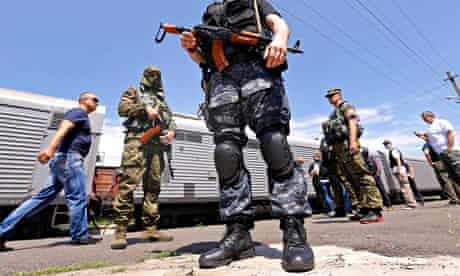 Pro-Russia separatists guarding the train station where bodies of MH17 victims have been taken