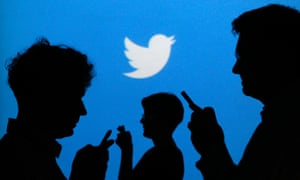 People holding mobile phones are silhouetted against a backdrop projected with the Twitter logo in this file illustration photo taken in Warsaw September 27, 2013.