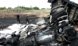 A rescue worker searches for bodies and wreckage at the crash site of MH17