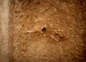 Two wrestlers practising the ancient Indian sport of Kushti in a pit  they had hacked into the ground two hours before