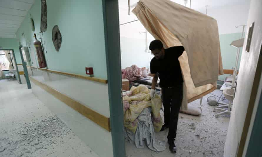 A Palestinian employee inspects damages at the Al-Aqsa Martyrs hospital in Deir al-Balah, in the central Gaza Strip