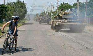 A cyclist watches as a convoy of Ukrainian armoured personnel carriers (APC) rides near the eastern Ukrainian city of Kramatorsk.