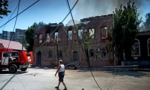 A man walks outside a house damaged by shelling in Luhansk, eastern Ukraine.