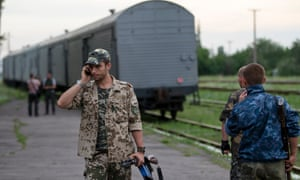 A pro-Russian rebel on the phone as a refrigerated train loaded with bodies of the passengers departs the station in Torez. ukraine mh17
