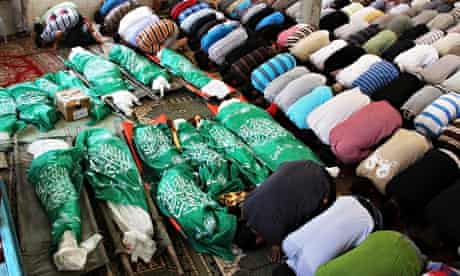 Palestinians pray over green flag-draped bodies