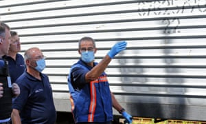 Forensic experts from the Netherlands and OSCE inspectors check refrigerated coaches containing bodies of victims.