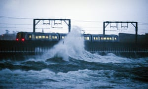 A train leaves Saltcoats station as a large wave crashes nearby on December 27, 2013 in Saltcoats, Scotland.