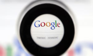 A Google search page is seen through a magnifying glass.