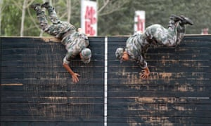 Chinese cadets conquer an obstacle of a  course during training at the People's Liberation Army Academy of Armored Forces Engineering in Beijing