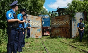 Police officers secure a refrigerated train loaded with bodies of the passengers of Malaysian Airlines flight MH17 as it arrives in a Kharkiv factory for a stop.