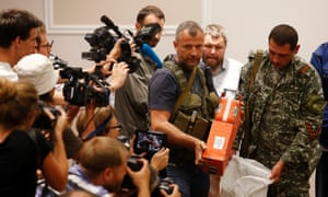 A pro-Russian separatist shows members of the media a black box belonging to Malaysia Airlines flight MH17, before its handover to Malaysian representatives, in Donetsk.