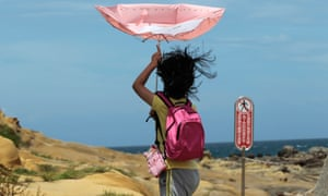 A girl struggles with winds from approaching Typhoon Matmo along the eastern coast of Keelung, northeastern Taiwan - the eye of Typhoon Matmo is expected to make landfall in eastern Taiwan early Wednesday