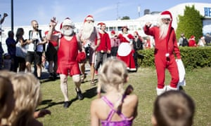 Santas are pictured at a Bellevue beach on July 22, 2014 in Copenhagen on the sidelines of the World Santa Claus Congress.