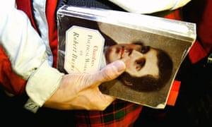 Man holds Robert Burns book