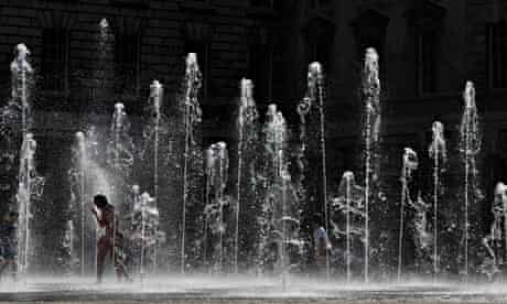 Visitors to Somerset House run through the courtyard fountains in central London