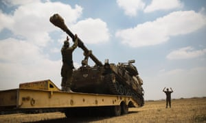 Israeli soldiers help offload a mobile artillery unit from the back of a truck in a staging area outside the Gaza Strip, 22 July, 2014.