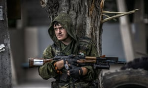 A pro-Russian separatist holds his gun as he takes cover behind a tree at a checkpoint in the northern outskirts of city of Donetsk. ukraine