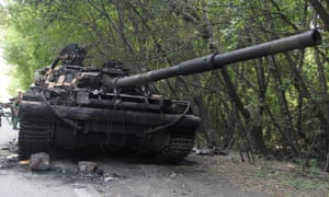 A Pro-Russian rebel stands near the burnt Ukrainian army tank on the outskirts of Donetsk. Ukraine