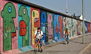 A cyclist passes along the Berlin Wall