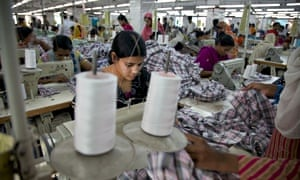 A worker sews plaid shirts on the production line of the Fashion Enterprise garment factory.