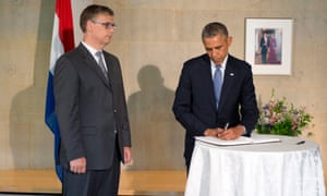 Barack Obama signs a condolence book for the victims of the Malaysia Airlines flight MH17 as Deputy Chief of Mission Peter Mollema (L) looks on.