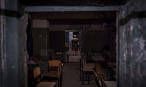 A woman walks through a makeshift bomb shelter in the basement of a school building in a residential area affected by shelling in Donetsk, Ukraine.