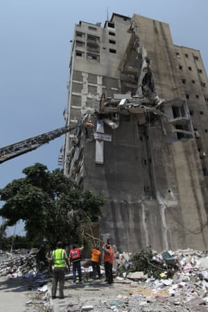 Palestinian members of civil defense inspect the rubble of Salam Tower following an Israeli airstrike on July 22, 2014 in Gaza, Palestine.