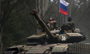 A pro-Russian rebel looks up while ridding on a tank flying Russia's flag, on a road east of Donetsk. ukraine
