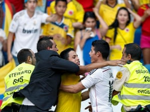 A fan is grabbed by security guards as he tries to embrace the new Real Madrid player James Rodríguez