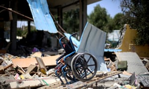 """A damaged wheelchair is seen in the ruins of building of Beit Lahia Disability and Rehabilitation Services destroyed in air attacks staged by Israel army within the scope of """"Operation Protective Edge"""" in Gaza City on 12 July, 2014."""