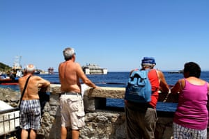 19 July 2014: Tourists watch the ongoing refloating operations on the Costa Concordia from the shore