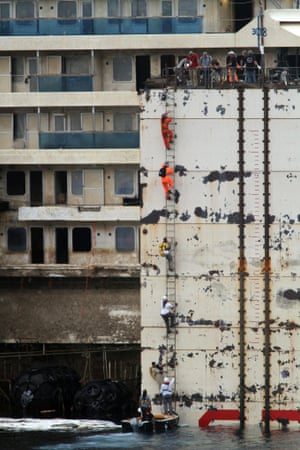 July 2014:  Workers climb onboard the ship during the refloating works