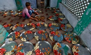 A man prepares plates of food at mosque in Ahmedabad