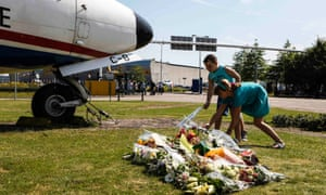 Two local children lay bouquets of flowers on the grass in front of a Dutch airplane in Eindhoven.