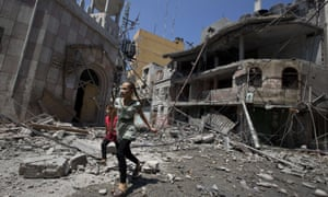 Palestinian girls walk amidst debris following an Israeli military strike in Gaza city, on 23 July, 2014.