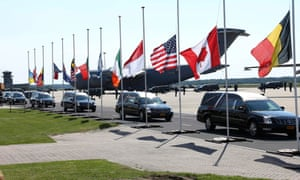 The convoy with the remains of the victims of Malaysia Airlines MH17 downed over rebel-held territory in eastern Ukraine, drives past international flags as it leaves Eindhoven airport.