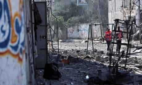 Palestinian medics walk past destroyed houses in the  Gaza City neighbourhood of Shujai'iyaduring