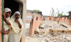Girls stand in the remains of their school in Maiduguri after it was burnt down by Boko Haram.