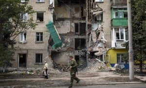 A pro-Russia rebel and a local resident walk past an apartment building damaged by rocket fire in Snizhne, Ukraine.