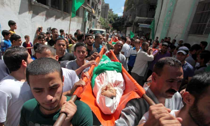 Mourners carry the bodies of three Palestinian teenage siblings.