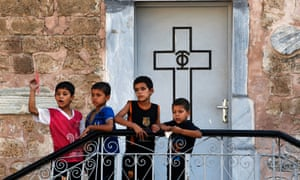 Palestinian boys on the steps of St Porphyrios church in Gaza City where hundreds of the displaced are being given shelter