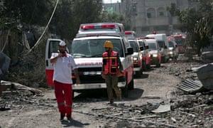 A Palestinian rescue convoy navigates rubble in Gaza City