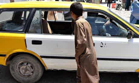 A youth looks at the taxi in which two Finnish women were shot in Herat, Afghanistan.