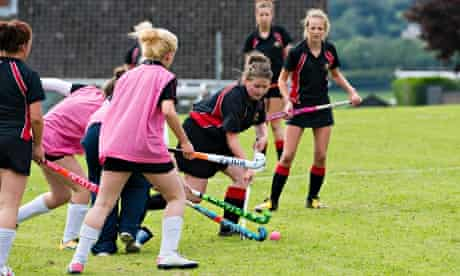 Teenage girls playing hockey outdoors at a secondary comprehensive school, Wales UK