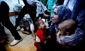 A Palestinian medic holds two children hurt in an Israeli strike on a UN school in Beit Hanoun, Gaza