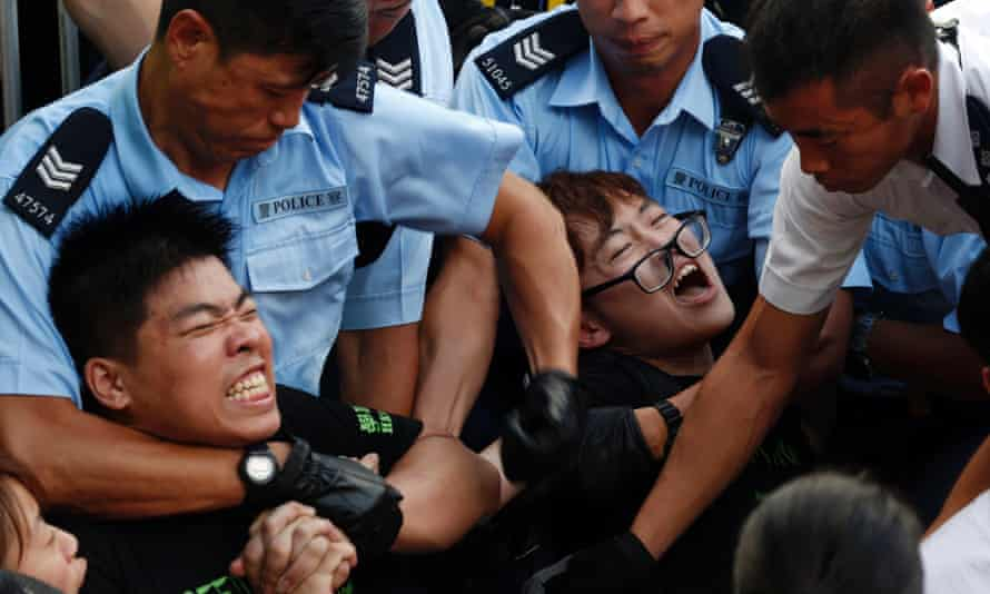 Protesters are taken away by police officers after hundreds of protesters staged a peaceful sit-ins.