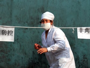 """A neighborhood committee worker guards the entrance to a roped-off apartment block behind a barrier that reads """"SARS Defence"""" in rural Beijing on 8 May 2003.  Communities across the city locked out non-residents in a desperate attempt to avoid the disease."""